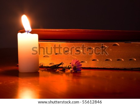 Closed Bible by candle light lying on a wooden table with small flower - stock photo