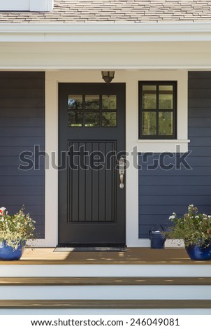 Closed Black Front Door with White Surrounding Door Frame and Blue Siding - stock photo