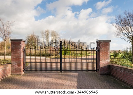 Closed black painted wrought iron gate between two masonry brick pillars at a newly created civilian cemetery. - stock photo