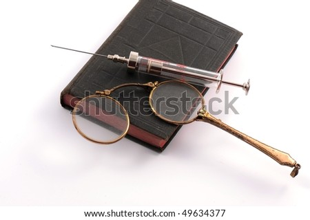 Closed book with eyeglasses and syringe