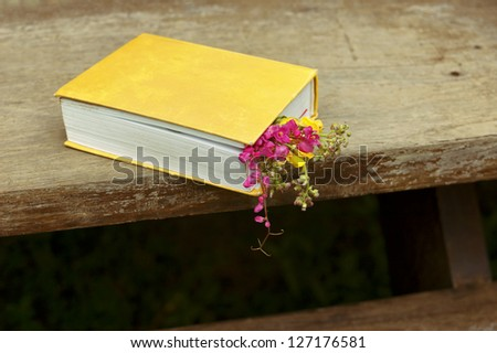 Closed book with flowers on wood table background horizontal - stock photo