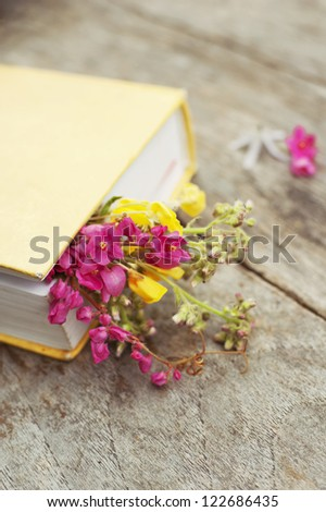Closed book with flowers on wood table background vertical - stock photo