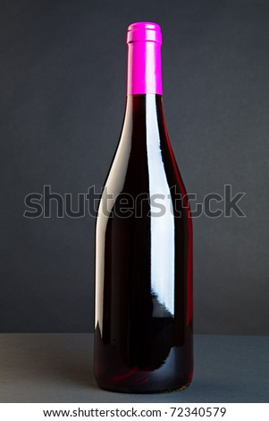 Closed bottle with red wine against a dark background