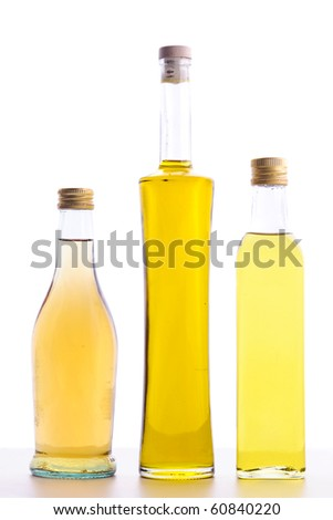 closed bottles of olive oil and bottle of wine vinegar isolated on white
