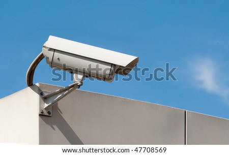 closed circuit tv surveillance camera against a light blue sky - stock photo