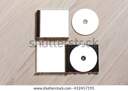Closed compact disc template with plastic box case with white isolated blank for branding design and open box with booklet. CD jewel case mock up with clean free space for on wooden table. Top view - stock photo