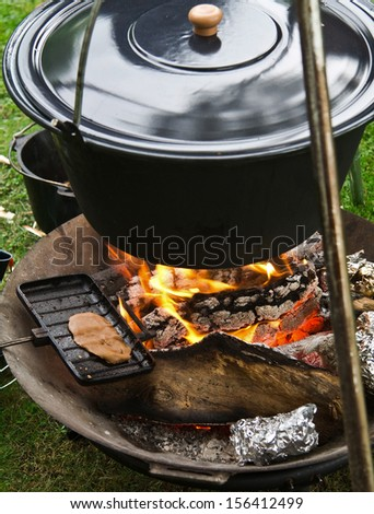 Closed cooking pot of fire - stock photo