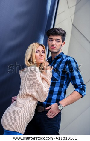 Closed couple of a handsome man and a sexy blonde woman looking away - stock photo