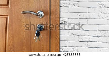 Closed door handle. Door lock with keys. Brown wooden door closeup at white brick wall. Modern interior design, door handle. New house concept. Real estate. - stock photo