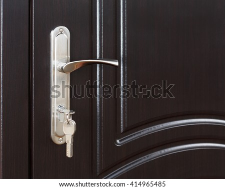 Closed door handle. Door lock with keys. Dark brown wooden door closeup. Modern interior design, door handle. New house concept. Real estate.  - stock photo