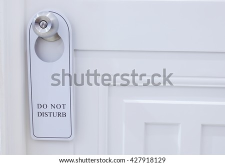 Closed door of hotel room with please do not disturb sign - stock photo