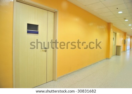 Closed doors along a lighted corridor - stock photo