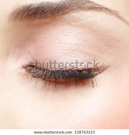 Closed eye of young caucasian woman with day makeup