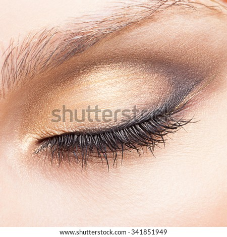 Closed eye of young Caucasian woman with day makeup - stock photo