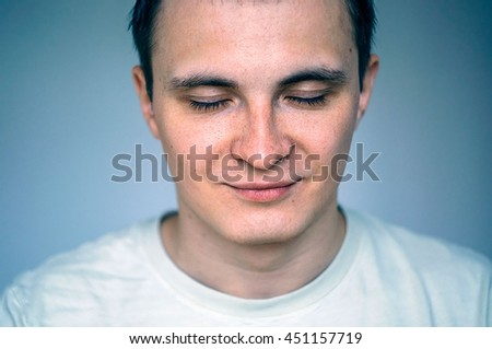 Closed eyes, not looking, portrait of young man. Head and shoulders shot, face close up. White t-short - stock photo
