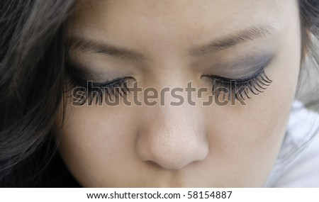 Closed eyes of young Asian-American woman with long eyelashes