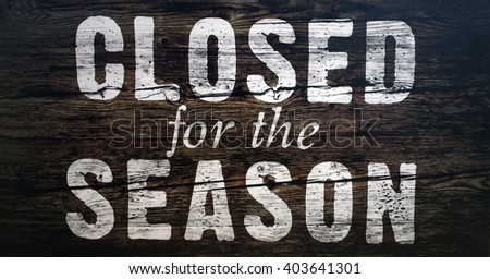 Closed for the season spray painted sign on wood. - stock photo