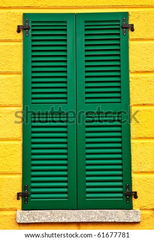 Closed green window shutters on yellow house facade. - stock photo