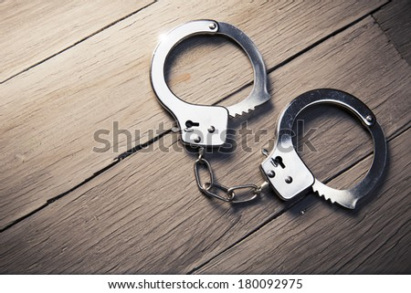 Closed handcuffs, Security concept on wooden background - stock photo