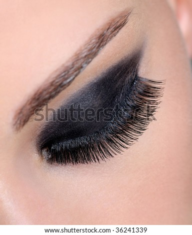 Closed human female eye with bright black eyeshadow and long false eyelashes - stock photo