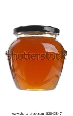 Closed jar of golden honey over white - stock photo