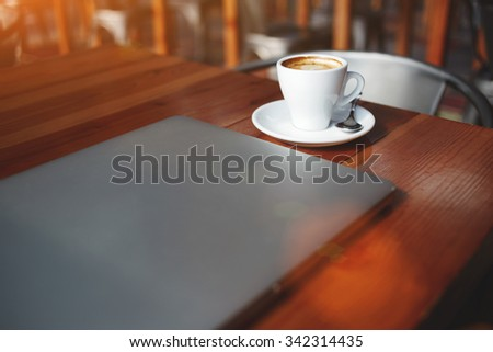 Closed laptop computer and cup of hot cappuccino lying on a wooden table in contemporary coffee shop interior, portable net-book with space for your brand, electronic business remote job via internet  - stock photo