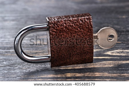 Closed lock with a key on a dark wooden background