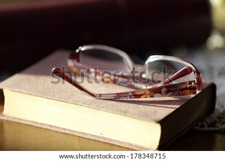 Closed old book and glasses, on home wooden table. - stock photo