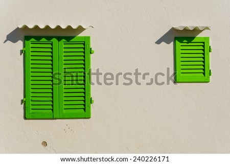 Closed old green window on white destroyed wall - Vintage house and typical mediterranean dwelling - stock photo
