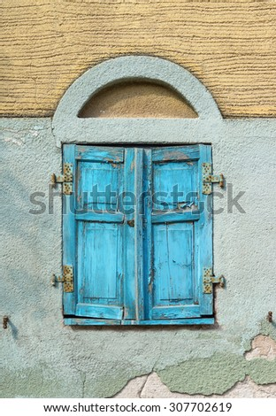 Closed, old, light blue window shutter of weathered wood in the facade of a dilapidated house. Taken in closeup.  - stock photo