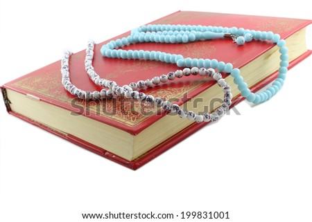 Closed old quran and paternosters - stock photo