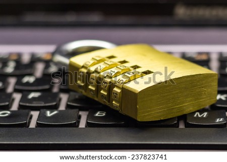 Closed or locked combination padlock on a laptop keyboard symbolizing data and computer security - stock photo