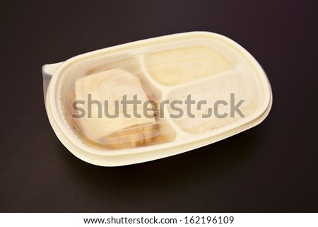 Closed package for freezing food or to go of parmesan chicken fillet, rice and mashed potatoes on brown background. - stock photo