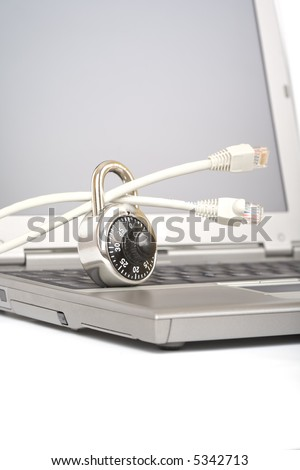 Closed padlock on network cables on a laptop - over a white background - stock photo