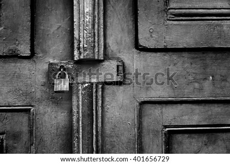 Closed padlock on wooden door, black and white tone, abstract dark feeling background