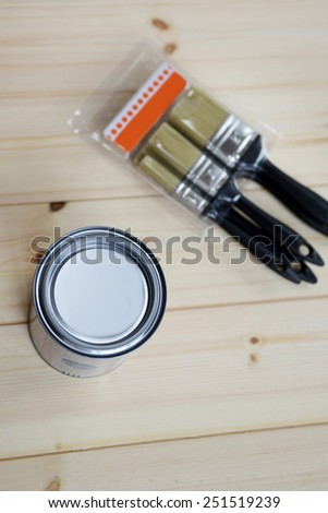 Closed Paint Can and Brushes in the box on Wooden Background  - stock photo
