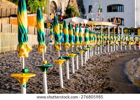 Closed parasols in a row on the Marina di Cassano beach. Piano di Sorrento. Italy - stock photo