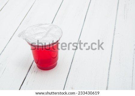 Closed plastic container for dairy foods with red clear jelly pudding with foil lid. Isolated on a white. - stock photo