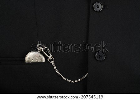 Closed pocket watch on a chain in a pocket of a black business suit as a backdrop composition - stock photo
