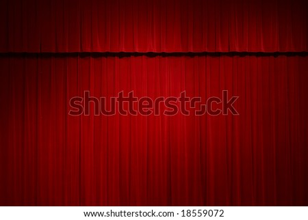 closed red stage curtains with a spot light on them - stock photo