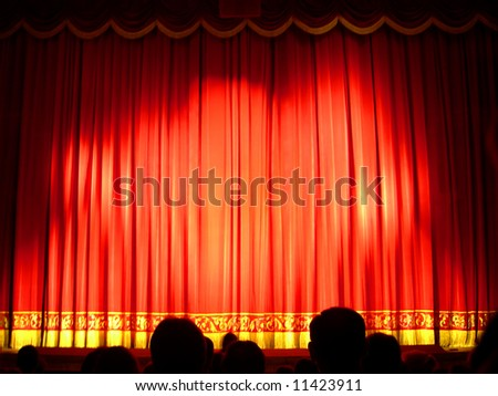 Closed red Theater stage curtain with dark silhouettes of people - stock photo
