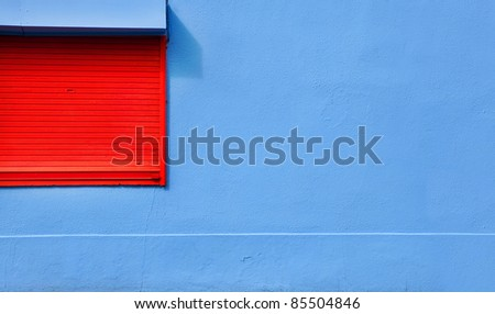 Closed red window on colorful blue wall - stock photo