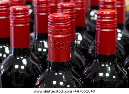 Closed red wine bottles standing in stores stock - stock photo
