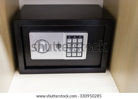 closed safe on shelf of cabinet in hotel room