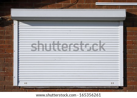 Closed serving hatch security shutters with brick background - stock photo
