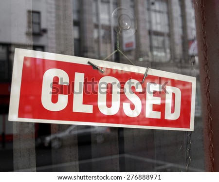 Closed sign in a shop showroom with reflections - red sign over desaturated background - stock photo