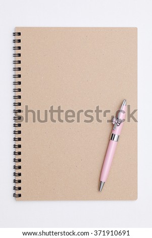 closed spiral notebook with ball point pen on white background