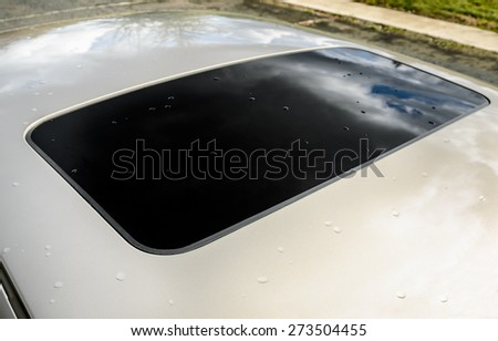 Closed sun roof with some raindrops of the modern car - stock photo