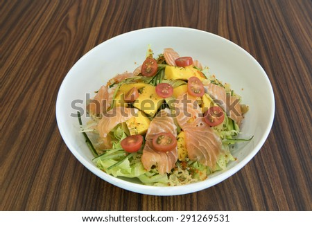 Closed up of a large white round bowl of salad with slices raw salmon and roe on fresh green vegetable with shredded cucumber and avocado, halved cherry tomatoes, and cubed mangoes.   - stock photo