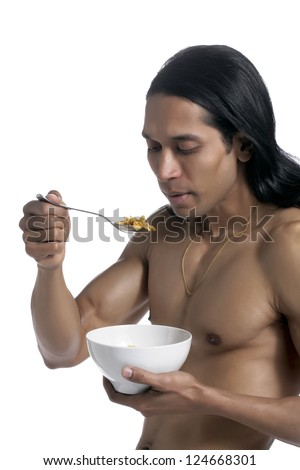 Closed up portrait of a muscular male eating some cereals over a white background